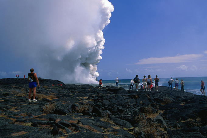 Tourists walk out to the smoking lava flow in the Hawaii Volcanos National Park.
