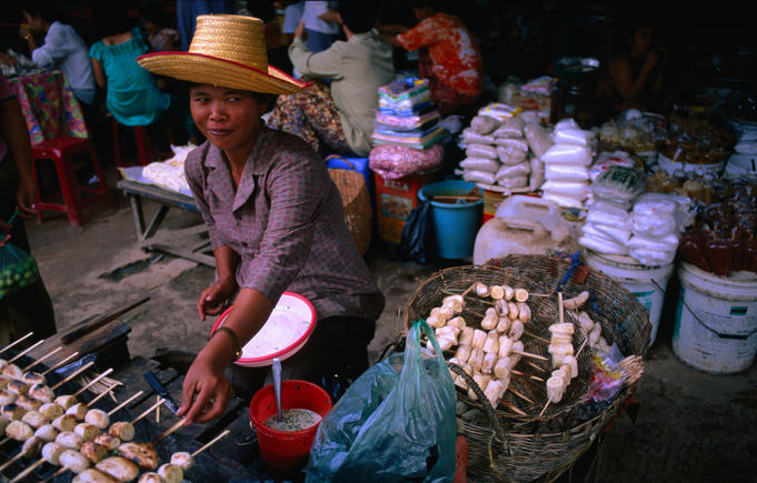 A vendor at the Siem Reap market cooks fried bananas, a favourite dessert.