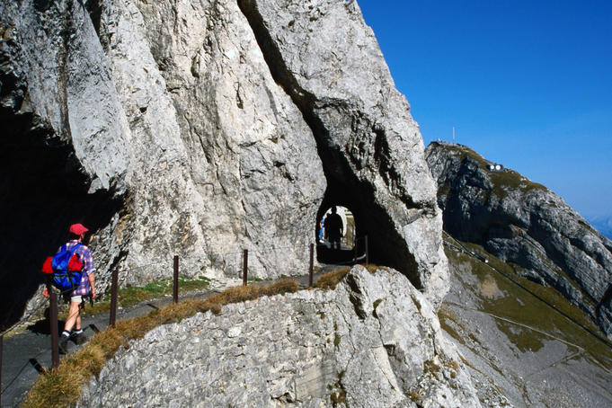 Hikers on Hohenweg with the tunnel leading from the top down to Lake Lucerne.