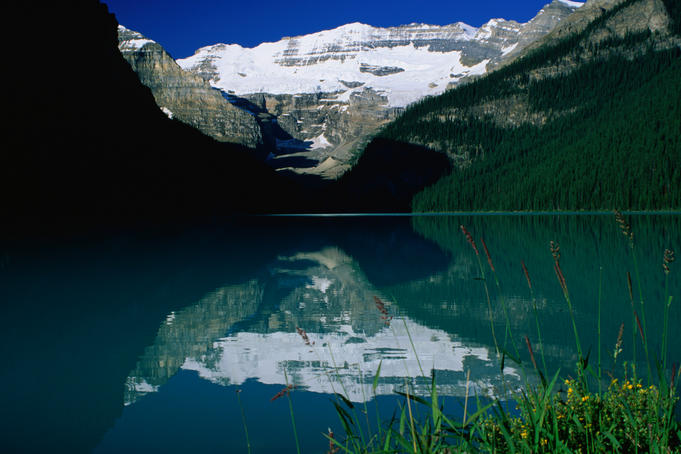 Serene and pristine reflections of snowcapped mountains surrounding Lake Louise, Alberta.
