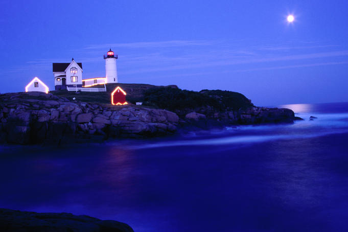 Nubble lighthouse alight underneath moon-lit sky.