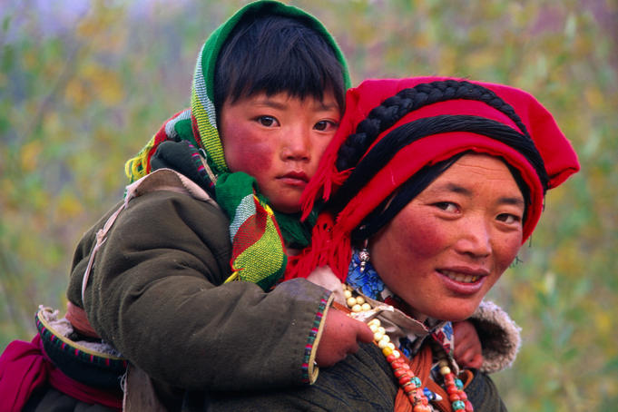 Tibetan woman carrying a young child on her back.