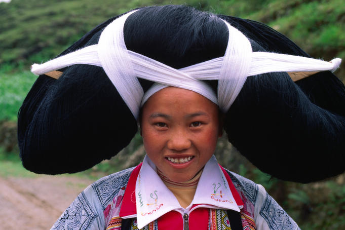 'Long Horn Miao' ethnic girl in traditional costume, with ancestral hair woven into headpiece, in Suoga village.
