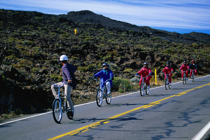 Cyclists coasting down the roads of Haleakala Crater.