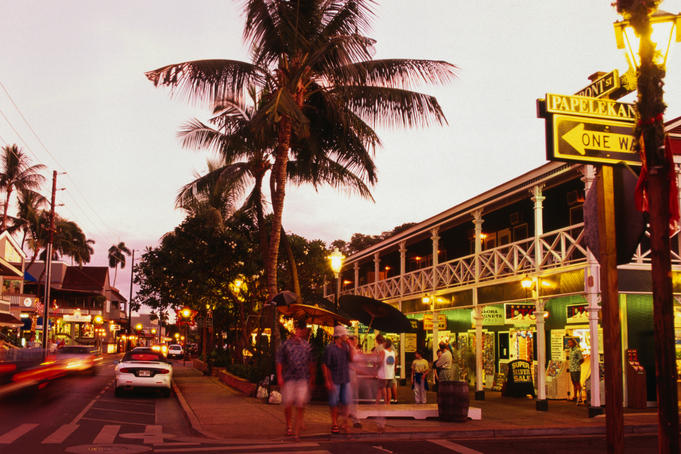 The Pioneer Inn and people shopping on Front Street at dusk.