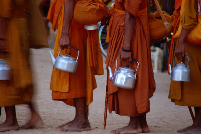 Saffron robed monks queue during an event at the ancient site of Angkor.