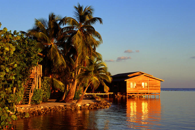 Early evening sunlight over the beach huts at Roatan's Cocoview Resort.
