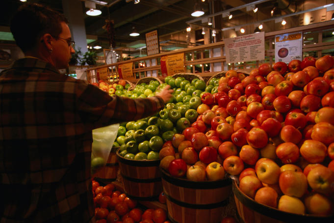 A shopper selecting apples in the Freshfields/Whole Foods Market on P Street.