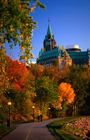 Autumn colours along path on Ottawa River bank, with Parliament building towering in the background