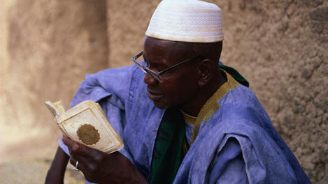 Man reading Koran outside Djenne Mosque