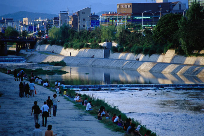 People walking along the banks of the Kamogawa River in Kyoto between shijo and sanjo.