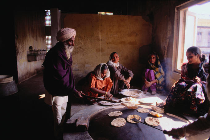 A group of worshippers cook chapatis in the kitchen of the Gurdwara Bara Sikh Temple in Kolkata.
