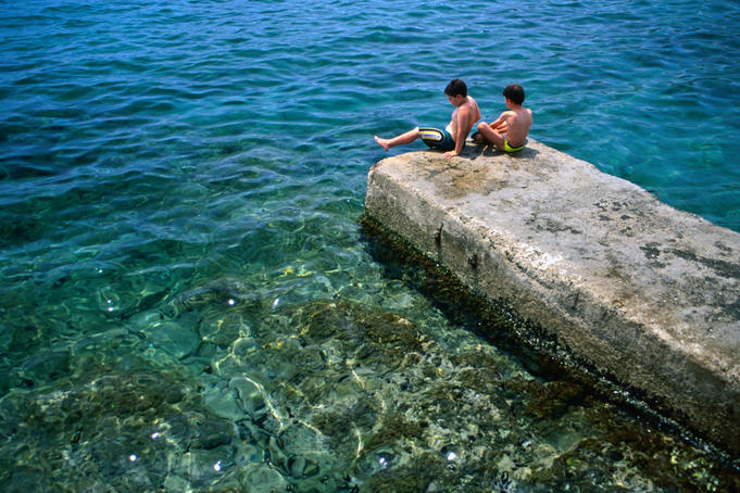 Two boys relax on a jetty surrounded by clear blue water, Cadaques