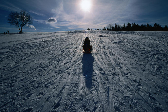 A woman on a sled on a snowy slope in the winter sun.