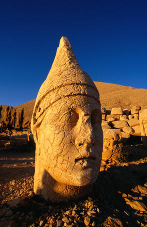 The earthquake damaged head of Heracles (or Hercules) at Nemrut Dagi (Mount Nemrut) with the burial mound of King Antiochu in the background.